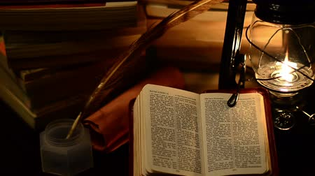 葡萄收获期 : A bible surrounded by books in a lamp light