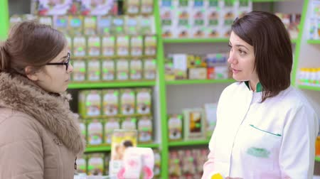 orvostudomány : Young female pharmacist in a drugstore having conversation with a custome Stock mozgókép
