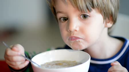 éhség : Little Boy eating cereal with milk and gets dirty