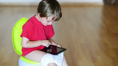 sanitário : Boy on potty using tablet pc