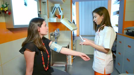 pomocník : Assistant Doctor measuring blood pressure to a patient