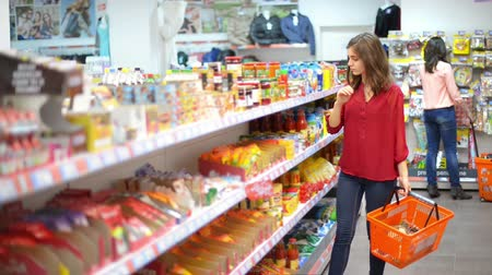 corredor : Happy woman with shopping basket choosing products in supermarket