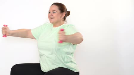 tłuszcz : Fat woman making exercises with dumbbells