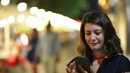 eszköz : Beautiful woman using a smartphone, city lights in the background