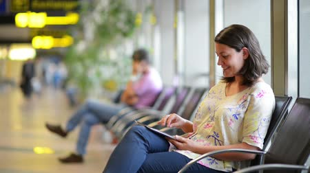 район : Young woman using a digital tablet in airport waiting area Стоковые видеозаписи