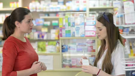 lojas : Young female pharmacist selling medicine to  customer in a drugstore Vídeos