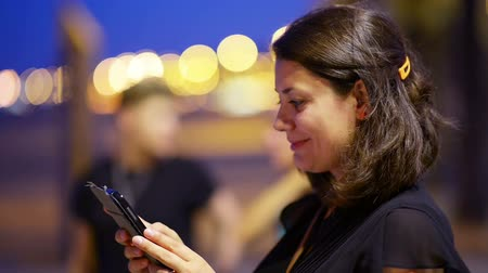 aplikacje : Young woman using a smartphone, with city lights in the background Wideo