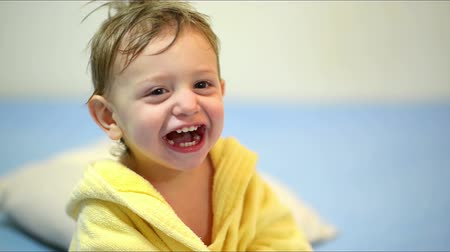 izgatott : Cute baby wearing a bath robe laughing after bath Stock mozgókép