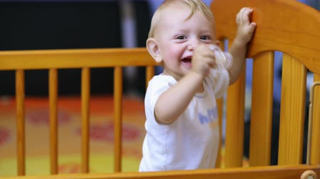 emzik : Cute baby laughing and showing his first teeth in a crib