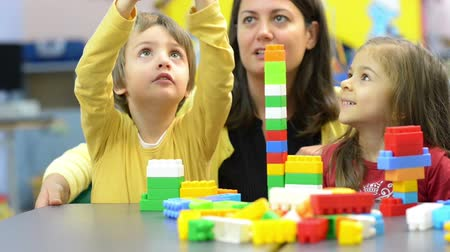 przedszkole : Kids and educator playing with plastic building blocks at kindergarten