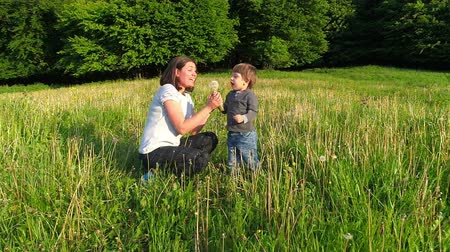 Happy kid with his mother blowing dandelion flower, slow motion