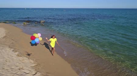 Happy girl holding balloons running on beach in summer day Stok Video