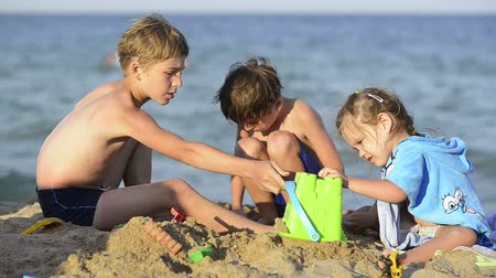 Three happy kids playing in sand on sea shore, summertime