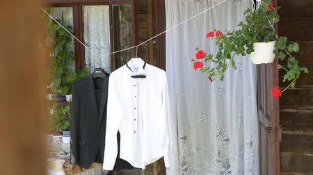 Clothes suit on hanger on a rustic porch, obsolete rural house Stok Video