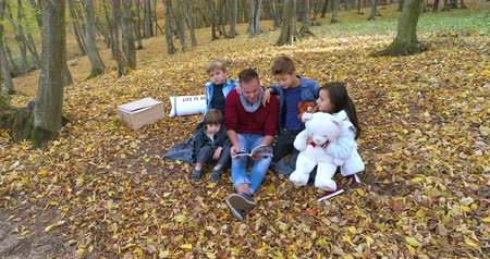 Happy family enjoying a fine autumn day in forest