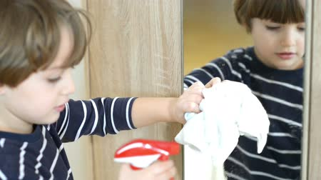 Cute funny little boy cleaning the mirror using cleaning spray