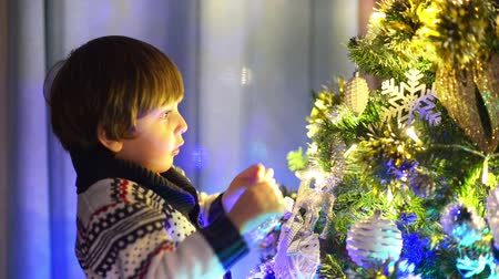 Cute little boy preparing for christmas, decorating christmas tree