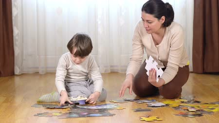 Cute kid solving a floor puzzle being helped by his mother