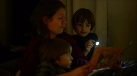 Mother reading bedtime stories, to her children Stok Video