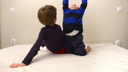 Cute happy kids playing in bed, parents dropping sheet over them Stok Video