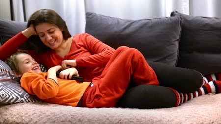 Loving mother spending time with her son, caressing him on sofa at home Stok Video