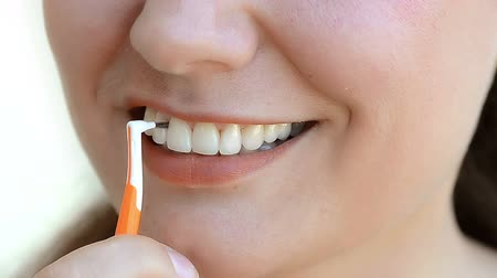 Young woman using interdental brush