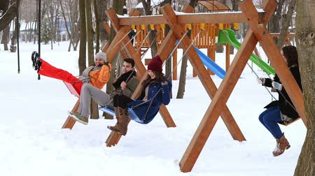 Young people swinging in a park, winter time