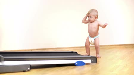 Cute baby learning to walk at home at home, exercising stand up