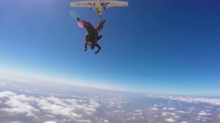 Parachutist jumping in tandem out of an sport airplane