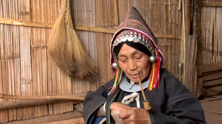 hill tribe : Old Akha woman smoking a pipe