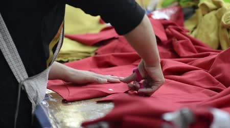 clothing : Close up shot of a woman cutting red fabric