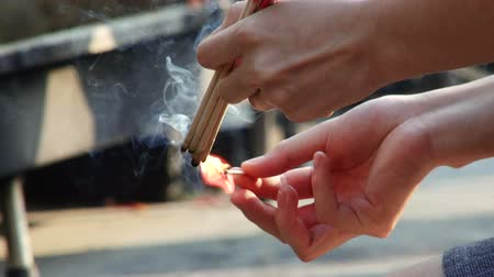 incenso : Close up of a person lighting incense for an offering at a Buddhist shrine in Thailand Stock Footage