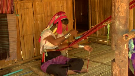 hill tribe : Karen long neck woman weaving on a back strap loom in a village in northern Thailand