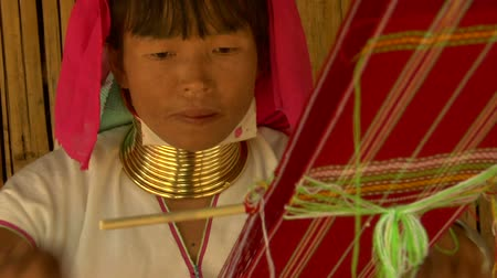 tajlandia : Karen long neck woman weaving on a back strap loom in a village in northern Thailand.