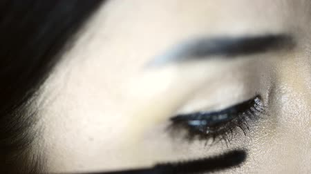 close up shot : Asian woman applying make up to her face. Close up