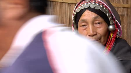hill tribe : Old Akha hill tribe woman smoking a bamboo pipe and spitting Stock Footage