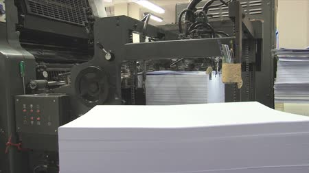 brochura : Stack of paper and a printing press