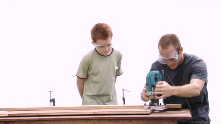 role model : Real construction worker teaching a teenage boy how to use a router safely. Could be an big brother, youth group leader or an uncle Stock Footage