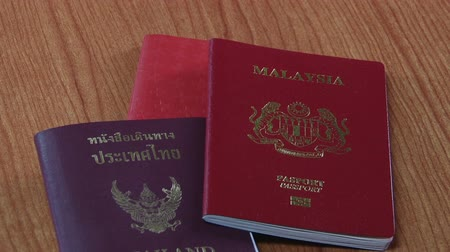 pas : Different coloured passports from seven different countries being placed on a table