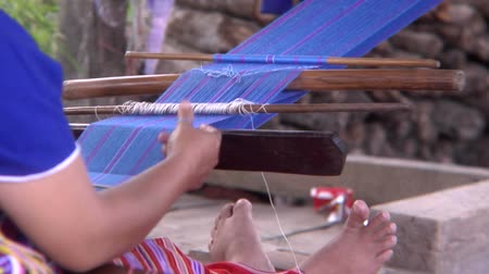 hill tribe : Karen hill tribe woman weaves cloth using a traditional back strap loom in a northern Thai village