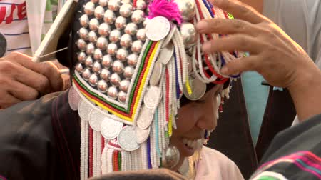 hill tribe : Young Akha hill tribe woman putting on her mothers traditional costume for the first time
