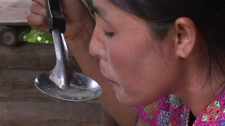 hill tribe : Zoom out from a Karen hill tribe woman tasting soup in the out door kitchen of her bamboo house. Part of a series on northern Thai hill tribe cooking Stock Footage