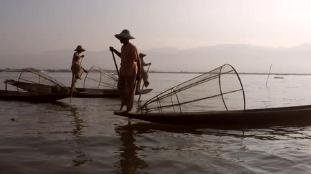 kürek çekme : Leg rowing fishermen on Inle Lake, Myanmar, show off their cultural traditions in their hand carved canoes.