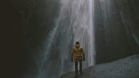 Man looking at waterfall in Iceland Vídeos