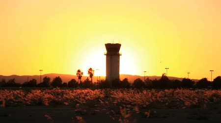 Sunset behind air traffic tower as helicopter flies by at Hollywood Burbank Airport Stock mozgókép