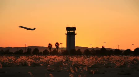 Plane takes off at sunset by air traffic tower at Hollywood Burbank Airport Stock mozgókép