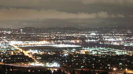 Bright time lapse shot overlooking the San Fernando Valley of Los Angeles with circling helicopters in the distance