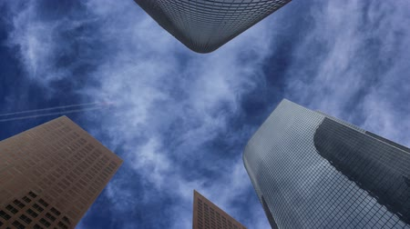 Low angle shot of skyscrapers in Los Angeles with a plane flying over