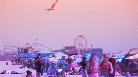Time lapse of a crowded beach with the Santa Monica Pier in the background