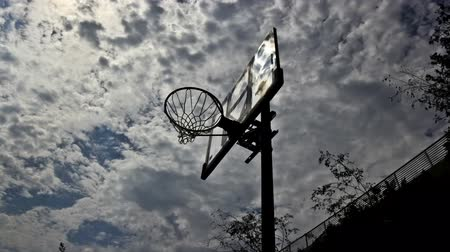 Outdoor basketball hoop low angle with clouds moving in time lapse